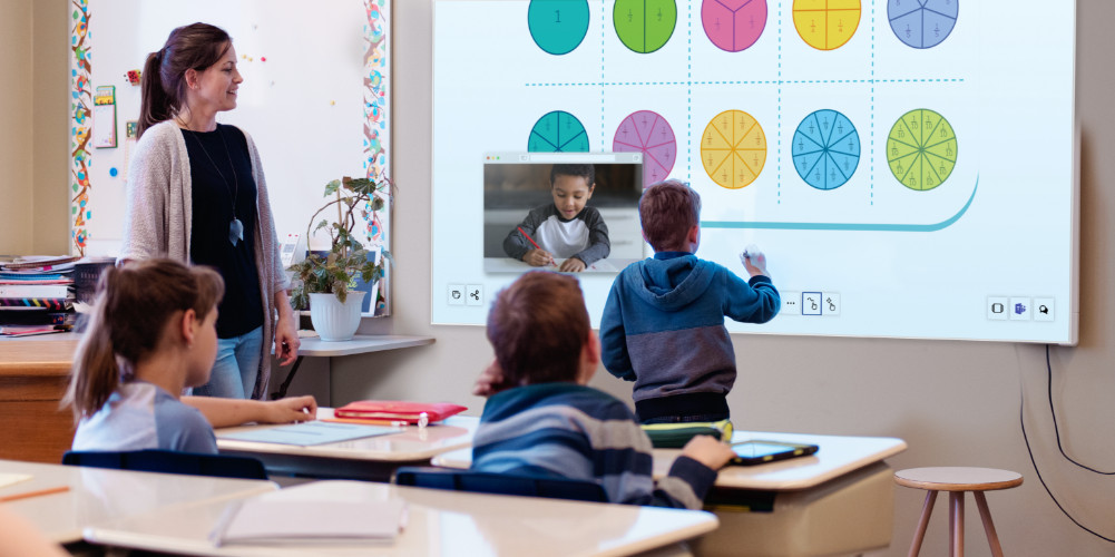 A teacher supervises a school boy writing the answer to a maths question on the wall using an Epson interactive projector
